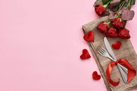 Romantic dinner. Close up of table setting with fresh red roses and decorative hearts Banque d'images - 117238280
