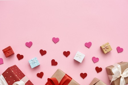 Big day for them. Cute gift boxes with decorative paper hearts on pink background Stockfoto