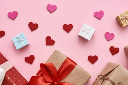 Love is in the air. Different types of gift boxes with decorative paper hearts on pink background.