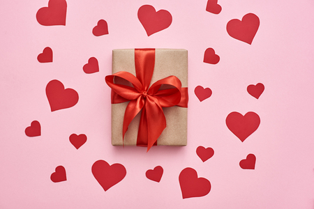 With love from heart...Top view of gift box with red ribbon and paper hearts Stockfoto