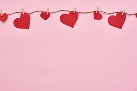 Valentine day...Red paper hearts hanging on the clothesline. Stockfoto