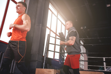 Warming up before training. Smilling and focused sportmen in sports clothing running in boxing gym Stok Fotoğraf - 117064705
