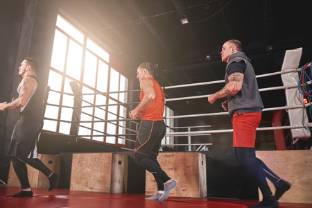Warming up their muscles. Smilling and focused sportmen in sports clothing running near boxing ring in gym Stok Fotoğraf - 117064715