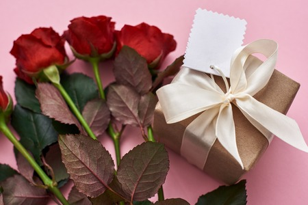 Perfect celebration. Close up view of gift box in kraft wrapping paper and fresh red roses Stockfoto