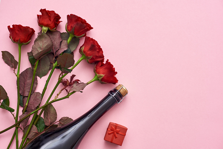 Celebrating special date. Surprise her with red roses, champagne and small red gift box