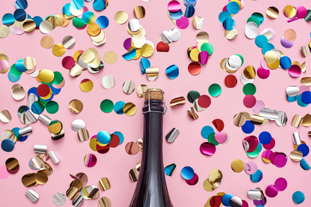 Party started! A bottle of champagne with glittering confetti on pink background. Standard-Bild - 117238341