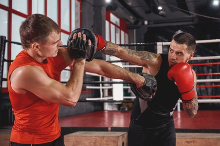 Counter punch. Strong tattooed athlete in sports clothing training on boxing paws with partner opposite boxing ring