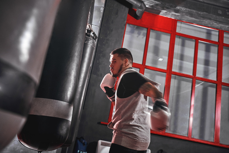 Training to be the best. Tattooed muscular athlete in sports clothing training hard on heavy punch bag before big fight in boxing gym Stock Photo