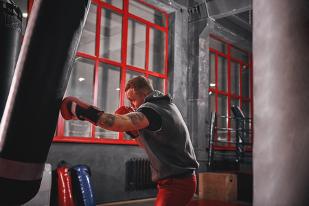 Way of life. Muscular sportsman in sports clothing exercising on heavy punch bag before fight in boxing gym Stock Photo