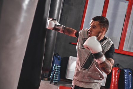 Pushing to the limit. Tattooed muscular athlete in sports clothing training hard on heavy punch bag before big fight in boxing gym