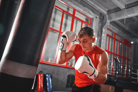 Killing workout. Muscular boxer with white boxing gloves in safeguard stand on red window background