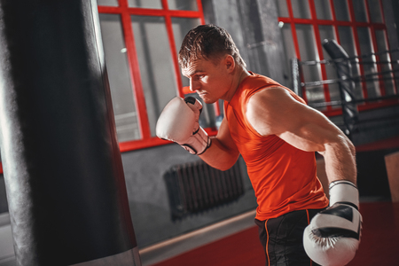 Stronger and faster. Handsome sportsman in sports clothing training on heavy punch bag in boxing gym