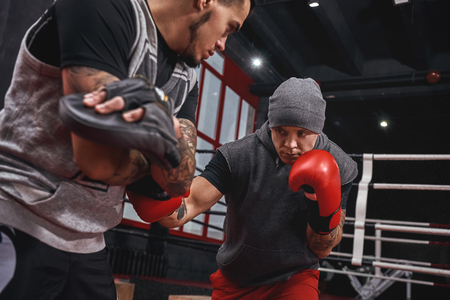 Close quarter boxing. Strong tattooed athlete in sports clothing training on boxing paws with partner opposite boxing ring Stock Photo
