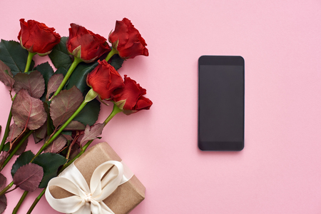 Day to celebrate their love. Top view of fresh red roses, gift box and black cellphone