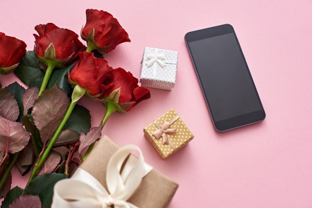 Application love. Impress her with fresh red roses, gift box and black cellphone Stockfoto