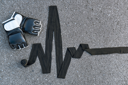 Sports boxing gloves with boxing bandages at the asphalt background