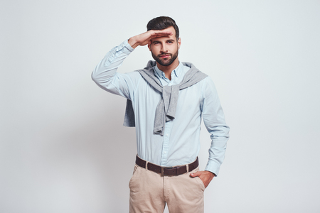Curiosity. Young bearded and handsome man in casual clothes is looking far away, searching for something while standing against grey background Banco de Imagens