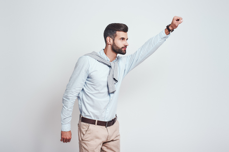 Superhero. Young bearded man is raising his hand up while standing against grey background. Enthusiasm concept.