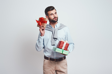 Buy gifts in advance. Good looking and smilling man is holding gifts on a grey background. 스톡 콘텐츠