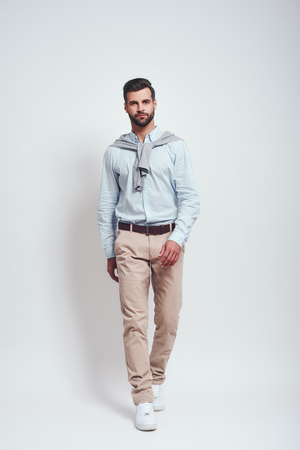Confidence in his style. Full length of a charming young man with beard in casual wear standing in studio on a grey background
