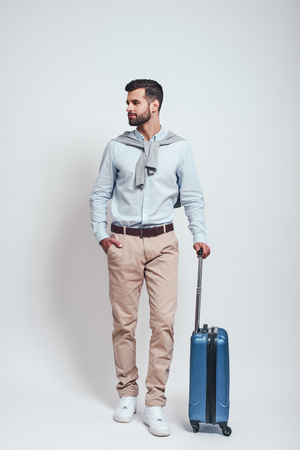 Ready to travel. Full length of handsome bearded young man with a suitcase keeping one hand in his pocket looking away. Travel concept. Archivio Fotografico