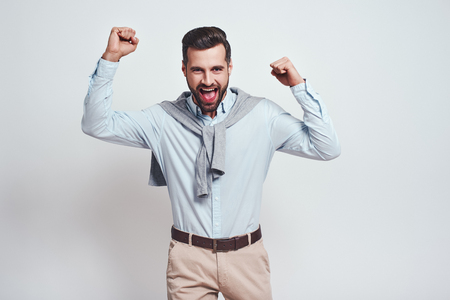 I did it! Happy young bearded man is celebrating his success with raised hands, standing on a grey background