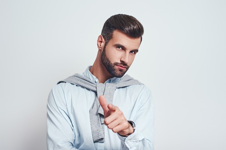 I choose you! Charming bearded man in casual wear gesturing and looking at you against grey background