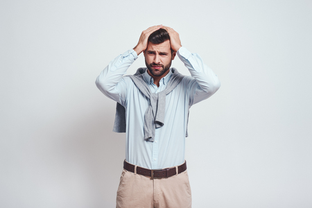 Emotional stress. Close-up portrait of confused young man keeping head in his hands and making a sad emotion while standing against grey background. Stockfoto