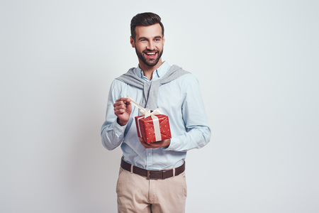 Portrait of a young smiling man opening gift box and looking at camera over grey background