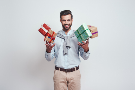 Gifts boom! Cheerful young man is holding gifts and feeling so happy standing on a grey background Stock Photo