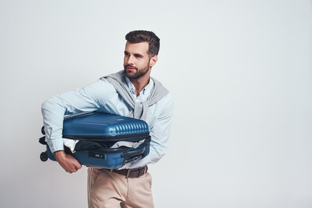 Ready to travel! Smiling handsome man is holding suitcase full of clothes while standing on a grey background. Travel concept