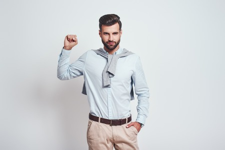 You can do it! Young attractive brunet in blue shirt is raising one hand clanched in fist above his head while standing against grey background