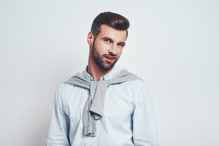 Really? Handsome young man in casual wear making doubt emotion while standing against grey background