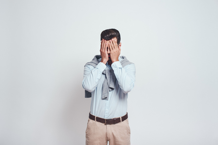 What did i do! Close-up portrait of disappointed man closing eyes with his hands on a grey background. Stress concept. Stockfoto - 117065564