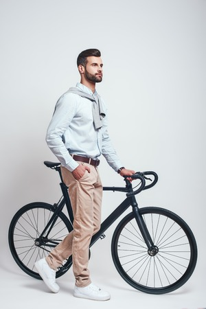 Convenient way to travel. Full length of a modern looking man with beard pulling his bicycle while standing in studio on a grey background