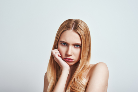 Bored. Upset young blonde woman looking at camera and making a sad face while standing in studio on a grey background Stock Photo