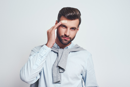 Bearded young man in casual wear is touching bandaid on his forehead and looking at camera while standing on a grey background.