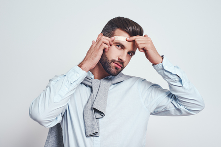Bearded young man in casual wear is putting bandaid on his forehead and looking at camera while standing on a grey background. Stock Photo