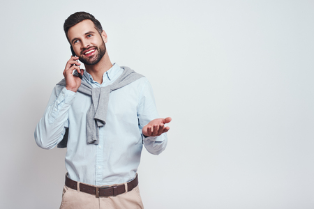 Glad to hear you! Attractive young man in casual wear is talking on the phone and smiling while standing against grey background. Positive emotion Banco de Imagens