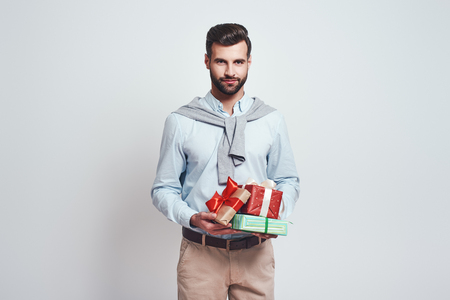 Preparing for holidays. Handsome smiling man is holding gifts for friends over gray background. Close-up