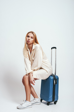 Waiting...Full length of pretty blonde woman sitting on her luggage and waiting for a flight. Travel concept
