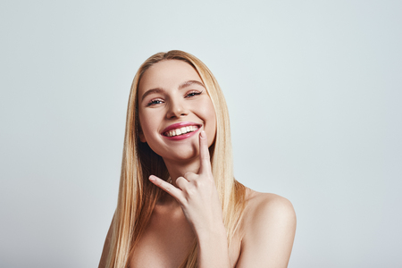 Feeling free. Cute blonde young woman gesturing and smiling at camera while standing on grey background. Playful mood