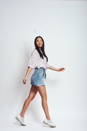 Carefree and happy. Full length of smiling young asian woman in bunny ears and casual wear on a grey background