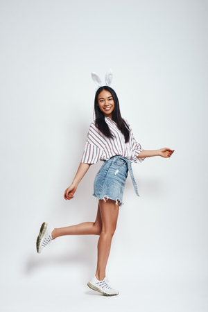 Cute bunny. Full length of attractive smiling asian woman in bunny ears and casual wear on a grey background Imagens
