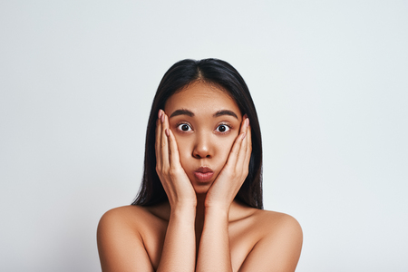 Frustrated asian woman is touching her head and looking at camera. Face expression