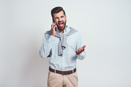 Angry bearded man is screaming while talking with somebody by smartphone. Negative emotions
