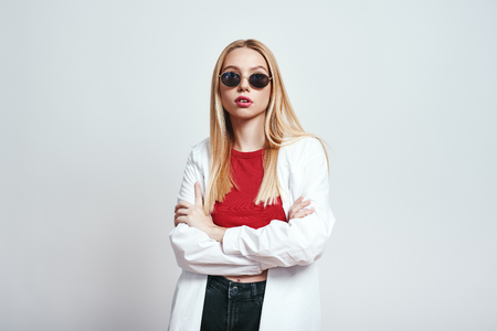 Beauty in everything. Young and stylish blonde woman in sunglasses with crossed arms standing against grey background. Fashion look