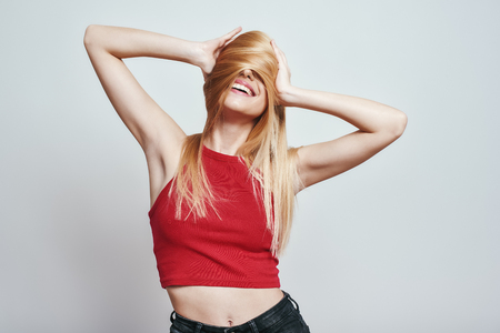 Feeling playful and happy. Slim woman in red tank top covering face with her hair and smiling while standing against grey background