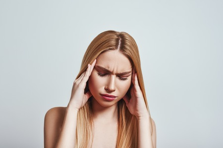 Terrible pain. Frustrated young woman touching a head with hands while standing in studio on a grey background. Pain concept Stock Photo
