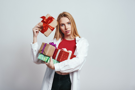 Birthday presents. Close up of cute young woman in white shirt carrying gift boxes while standing against grey background